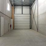 Op deze foto staat een deel van de bedrijfsruimte / hal, met de handbediende overhead-deur. Rechtsboven zie je het raam van de kantoorruimte op de eerste verdieping