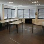 Kantoorruimte met antraciet tegelvloer, systeemplafond met verlichtingsarmaturen