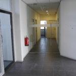 Centrale hal met antraciet tegelvloer, glazen deur, systeemplafond met verlichtingsarmaturen