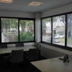 kantoorruimte met antraciet project tapijt, systeemplafond met verlichtingsarmaturen en uitzicht naar buiten