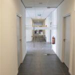 hal op de begane grond met glazen toegangsdeur, antraciet tegelvloer en systeemplafond