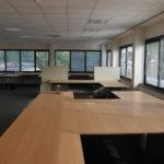 kantoorruimte op de eerste verdieping met meubilair, antraciet project tapijt en systeemplafond met verlichtingsarmaturen