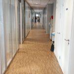 Gangpand op de eerste verdieping, gedeelte De Admiraal, met houtenprint vloerbedekking, glazen wanden, systeemplafond met verlichtingsarmaturen.