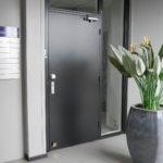 De entree zelfstandige unit tweede verdieping met naambordje, tegelvloer en glasinzet naast de deur