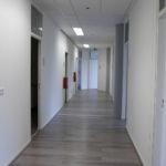 Een gedeelte van de gang, met hout-print vloer-afwerking, systeemwanden, systeemplafonds met verlichtingsarmaturen