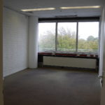 Een kantoorkamer op het noorden, met antraciet vloerbedekking, verwarming, systeemplafond met verlichtingsarmatuur