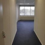 doorkijk naar een van de kantoorkamers met witte systeemwanden, blauw projecttapijt, systeemplafond met verlichtingsarmaturen