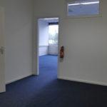 Doorkijkje in kleine kantoorkamer met blauw project tapijt, systeemplafond met verlichtingsarmaturen.