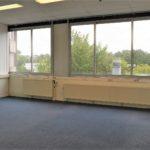 Een grote kantoorrkamer met antraciet project tapijt, systeemplafond met verlichtingsarmaturen en verwarmingselementen onder de ramen.