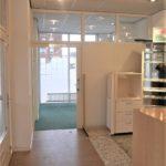 Binnenzijde winkelruimte met systeemplafond met verlichtingsarmaturen, gladde tegelvloer en systeemwanden met glasinzet.